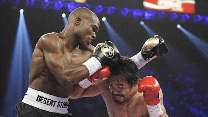 Manny Pacquiao, right, from the Philippines, and Timothy Bradley, from Palm Springs, Calif., trade blows in the first round of their WBO welterweight title fight Saturday, June 9, 2012, in Las Vegas. (AP Photo/Chris Carlson)