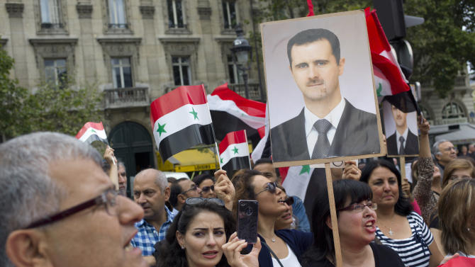 Protestors hold placard showing Syrian President Bashar Assad and Syrian flags during a demonstration against French and foreign military involvement in Syria, in Paris, Saturday, Aug. 31, 2013. The United States is considering launching a punitive strike against the regime of Syrian President Bashar Assad, blamed by the U.S. and the Syrian opposition for an Aug. 21 alleged chemical weapons attack in a rebel-held suburb of the Syrian capital of Damascus. (AP Photo/Thibault Camus)