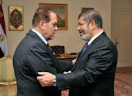 Egypt's new president-elect Mohamed Morsi (R) shake hands with Prime Minister Kamal al-Ganzuri in the Al-Ittihadiya presidential palace in Cairo in a picture courtesy of the Egyptian presidency