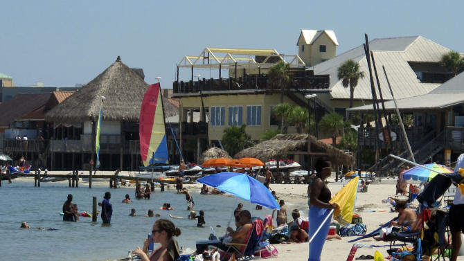 FILE - This Aug. 28, 2011 file photo shows tourists as they sit on the beach at Pensacola Beach, Fla. The white sand beaches and turquoise waters of Florida's Panhandle draw millions of visitors each year, from college spring breakers to families on summer vacation. (AP Photo/Melissa Nelson, file)
