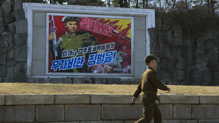 """A North Korean soldier passes by roadside propaganda depicting a North Korean soldier killing a U.S. soldier in Pyongyang, North Korea on Wednesday, April 10, 2013. The poster reads in Korean """"Life or Death Battle. Merciless Punishment to U.S. Imperialists and Puppet Traitors."""" (AP Photo/David Guttenfelder)"""