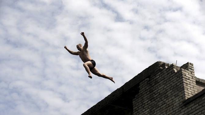 A man jumps into water from the roof of Murru prison, an abandoned Soviet prison, in Rummu quarry