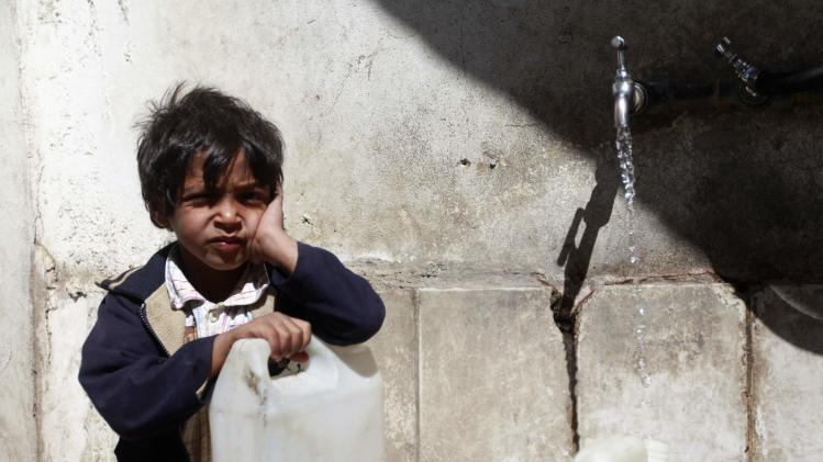 A boy fills up his jug of water, joining other children on their daily search for potable water in Sanaa