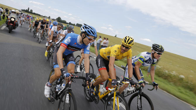 David Zabriskie of the US, Fabian Cancellara of Switzerland, wearing the overall leader's yellow jersey, and Stuart O'Grady of Australia, from left to right, ride in the pack during the fifth stage of the Tour de France cycling race over 196.5 kilometers (122 miles) with start in Rouen and finish in Saint-Quentin, France, Thursday July 5, 2012. Zabriskie is one of five former teammates of seven-time Tour de France winner Lance Armstrong who, according to Dutch newspaper De Telegraaf, have struck a deal with the US anti doping agency USADA to admit to using doping and to give evidence against Armstrong in exchange for what is considered a light punishment, a 6-month ban on professional cycling. (AP Photo/Laurent Cipriani)
