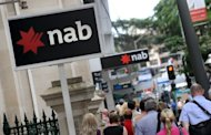 This file photo shows National Australia Bank (NAB) signs in central Brisbane. NAB on Monday said it plans to restructure its struggling British business, slashing more than 1,400 jobs at the loss-making arm by 2015