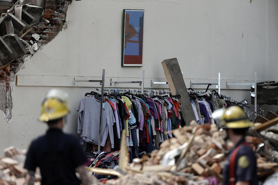 Firefighters view the scene of a building collapse, Thursday, June 6, 2013, in Philadelphia. On Wednesday, the building under demolition collapsed onto a neighboring thrift store, killing six people and injuring 14, including one who was pulled from the debris nearly 13 hours later. (AP Photo/Matt Rourke)