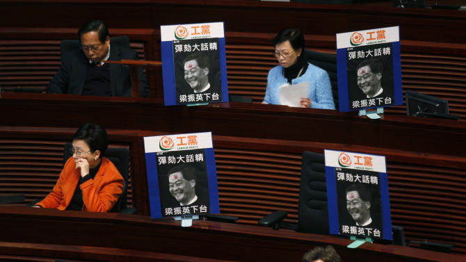 """Pro-democracy members of Hong Kong's legislature display pictures of Hong Kong's leader Leung Chun-ying with the words """"Impeach liar, Leung Chun-ying step down"""" at the Legislative Council in Hong Kong Wednesday, Jan. 9, 2013. Lawmakers were making a symbolic attempt Wednesday to impeach Hong Kong's Beijing-backed leader, the latest sign of the widening gulf between the semiautonomous southern Chinese city and its political masters in Beijing. (AP Photo/Kin Cheung)"""