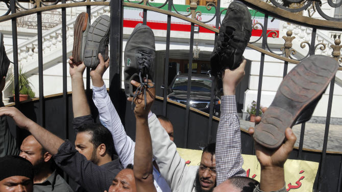 Egyptian protesters raise their shoes and shout anti-Iran slogans during a protest at the residence of Iran's top diplomat to protest the Egyptian government's attempt to improve ties with Tehran in Cairo, Egypt, Friday, April 5, 2013. (AP Photo/Amr Nabil)