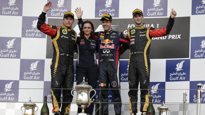 Red Bull driver Sebastian Vettel of Germany, winner, second right, second placed Lotus driver Kimi Raikkonen of Finland, left, and Lotus driver Romain Grosjean of France, right, stand on the winner's podium after the Bahrain Formula One Grand Prix in Sakhir, Bahrain, Sunday, April 21, 2013. (AP Photo/Hassan Ammar)