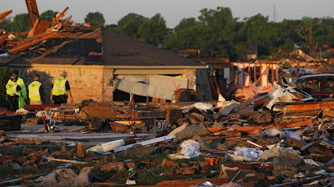 At sunrise, police patrol a partially-destroyed row of houses adjacent to a group of homes completely leveled on Monday when a tornado moved through Moore, Okla., Wednesday, May 22, 2013. The huge tornado roared through the Oklahoma City suburb, flattening a wide swath of homes and businesses. (AP Photo/Brennan Linsley)