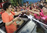 Former Philippine first lady Imelda Marcos hands out candies and calendars from a car in Manila's Pandacan district in January 2012. Marcos has declared her net worth at $22 million, parliament records show, as she continues to fight the government over her assets more than two decades after the end of her dictator husband's reign