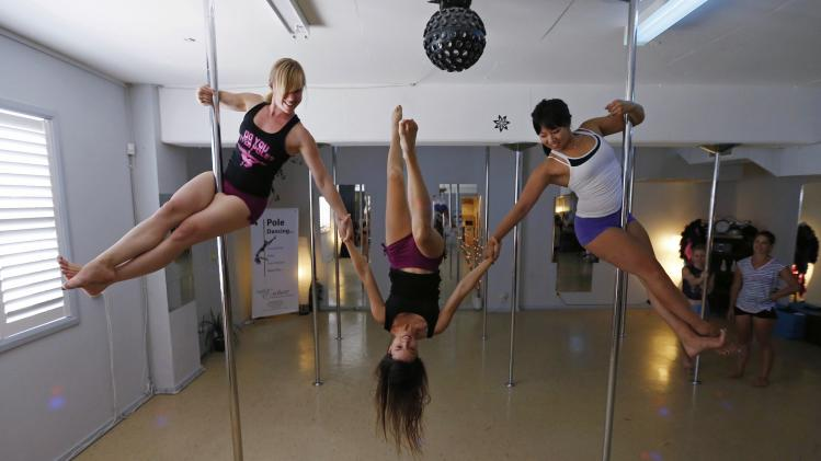 Women practise a pole dancing move during an International Women's Day event at a women's-only pole dancing fitness studio in Sydney
