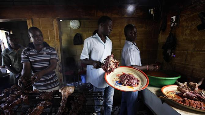 In this photo taken on Saturday, Oct. 20, 2012, men grill meat into suya in Lagos, Nigeria.  As night falls across Nigeria, men fan the flames of charcoal grills by candlelight or under naked light bulbs, the smoke rising in the air with the smell of spices and cooking meat. Despite the sometimes intense diversity of faith and ethnicity in this nation of 160 million people, that thinly sliced meat called suya, is eaten everywhere. (AP Photo/Sunday Alamba)