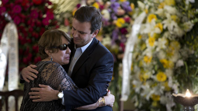 """Vera Lucia, wife of Brazilian architect Oscar Niemeyer, left, embraces Rio de Janeiro's Mayor Eduardo Paes next to the coffin containing the remains of Niemeyer, at the """"Palacio da Cidade"""" or """"City Palace"""", in Rio de Janeiro, Friday, Dec. 7, 2012. Niemeyer, 104, the groundbreaking architect who designed Brazil's futuristic capital and much of the United Nations complex, died Wednesday night in Rio de Janeiro, the seaside city where he was born and where his remains will be buried. (AP Photo/Felipe Dana)"""