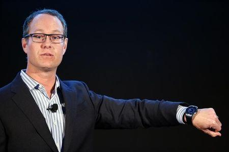 Qualcomm President Aberle shows a watch made with a Qualcomm snapdragon processor during a press conference