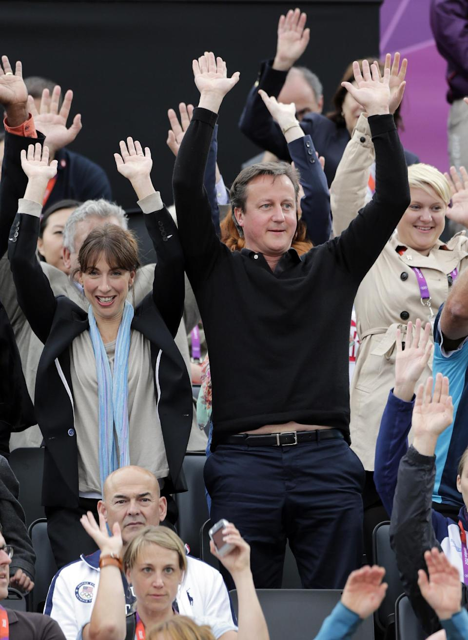 British Prime Minister David Cameron, right, participates in the wave cheer during a women's semi-final beach volleyball match between China and the United States at the 2012 Summer Olympics, Tuesday, Aug. 7, 2012, in London. (AP Photo/Dave Martin)