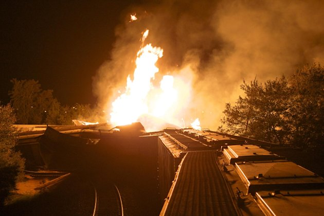 Flames rise from a derailed freight train early Wednesday July 11, 2012 in Columbus, Ohio. Part of a freight train derailed and caught fire in Ohio's capital city early Wednesday, shooting flames skyward into the darkness and prompting the evacuation of a mile-wide area as firefighters and hazardous materials crews worked to determine what was burning and contain the blaze.(AP Photo/Chris Mumma)