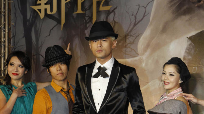 """Taiwan performer Jay Chou, center, poses for photographers during a press conference announcing his new CD """"Opus 12"""" in Taipei, Taiwan, Thursday, Dec. 27, 2012. (AP Photo/Wally Santana)"""
