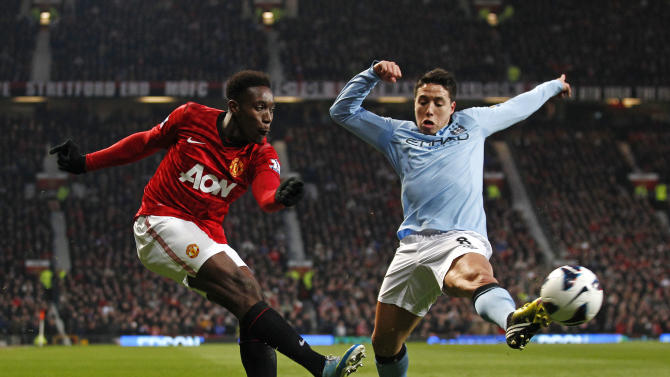 Manchester United's Danny Wellbeck, left, gets in a cross despite the challenge of Manchester City's Samir Nasri during their English Premier League soccer match at Old Trafford Stadium, Manchester, England, Monday April 8, 2013. (AP Photo/Jon Super)