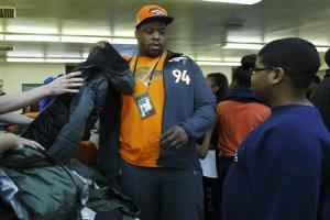 """Denver Broncos defensive tackle Terrance Knighton helps a kid to try on a jacket as part of an activity with The Knights of Columbus called """"Coats for Kids"""" in Jersey City"""