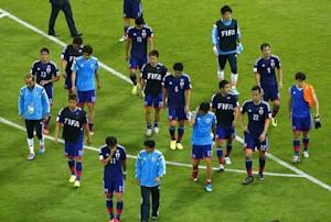 Team Japan walk off the pitch after the 2014 World Cup Group C soccer match between Ivory Coast and Japan at the Pernambuco arena in Recife