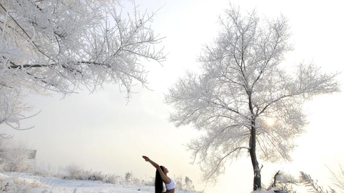 Xie Xiaoming, 26-year-old owner of a yoga club, practices yoga in thin clothes near trees covered by frosty fog on the snow-covered banks of Songhua River in Jilin