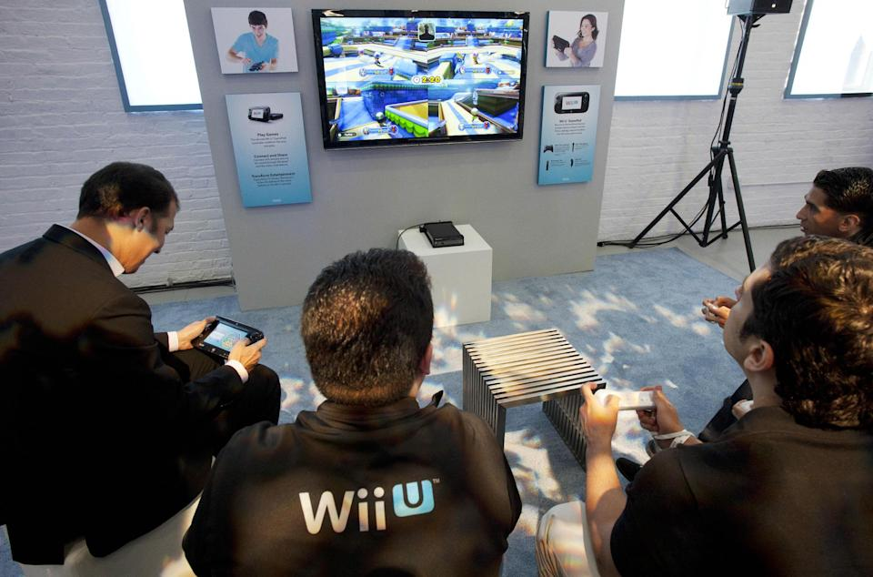 FILE - In this Thursday, Sept. 13, 2012 file photo, people demonstrate the Nintendo's Wii U GamePad and console in New York. Nintendo seeks to shake up gaming again with the Wii U touchscreen controller. (AP Photo/Mark Lennihan, File)