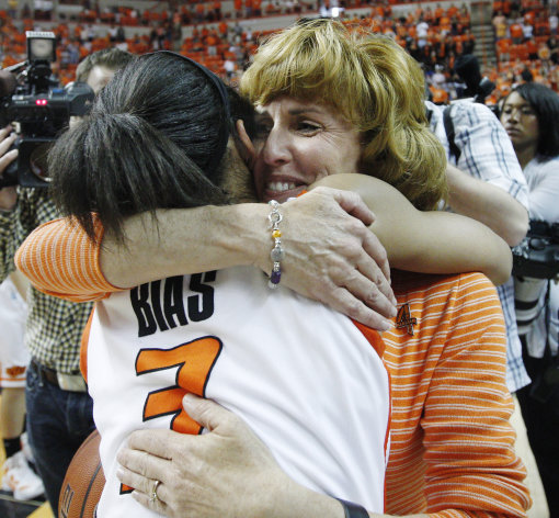 Shelley Budke, right, the widow of Kurt Budke, the Oklahoma State women's basketball coach who died in a plane crash in November of 2011, hugs guard Tiffany Bias (3) following Oklahoma State's 75-68 victory over James Madison in the WNIT Championship basketball game in Stillwater, Okla., Saturday, March 31, 2012. (AP Photo/Sue Ogrocki)