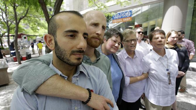 From left, plaintiffs Moudi Sbeity and Derek Kitchen, Kate Call, Laurie Wood and Kody Partridge, five of the six people who brought the lawsuit against the Utah's gay marriage ban, stand together at a news conference outside their lawyer's office Wednesday, June 25, 2014, in Salt Lake City. Call's partner, Karen Archer, was not able to attend. On Wednesday, June 25, 2014, a federal appeals court in Denver ruled that states must allow gay couples to marry, finding the Constitution protects same-sex relationships. The decision from a three-judge panel in Denver upheld a lower court ruling that struck down Utah's gay marriage ban. (AP Photo/Rick Bowmer)