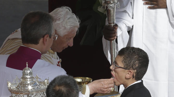 Jake Finkbonner, of Ferndale, Washington, receives the holy communion from Pope Benedict XVI during a canonization ceremony, in St. Peter's Square, at the Vatican, Sunday, Oct. 21, 2012.  Finkbonner was infected with a flesh-eating bacteria in 2006, when he was five years old, and his prognosis was so grave that his parents had last rites performed and were discussing donating his organs. The Vatican determined that Jake's cure was a miracle due to the intercession of Kateri Tekakwitha, a 17th century Native American who is among seven people who were declared saints during the ceremony.  (AP Photo/Alessandra Tarantino)