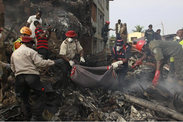 Rescue workers collect bodies from the scene of a plane crash in Lagos, Nigeria, Monday, June 4, 2012. A passenger plane carrying more than 150 people crashed in Nigeria's largest city on Sunday,