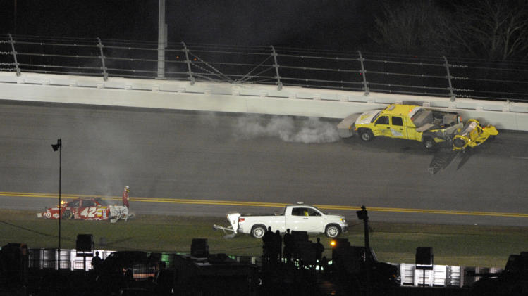 Juan Pablo Montoya, left, of Colombia, walks away from his car after it collided with a jet dryer during the NASCAR Daytona 500 auto race at Daytona International Speedway in Daytona Beach, Fla., Monday, Feb. 27, 2012. (AP Photo/Phelan M. Ebenhack)