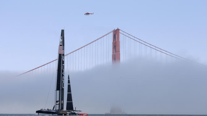 An Oracle Team USA catamaran makes its way past the Golden Gate Bridge in the fog during training for the America's Cup, Wednesday, July 3, 2013, in San Francisco. Opening ceremonies for the sailing event are scheduled for Thursday. (AP Photo/Eric Risberg)