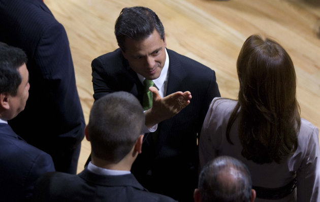 Mexico's President-elect Enrique Pena Nieto, center, of the Institutional Revolutionary Party (PRI), gestures as his wife Angelica Rivera stands at right during a ceremony at the Federal Electoral Tribunal (TRIFE) in Mexico City, Friday, Aug. 31, 2012. The TRIFE declared Pena Nieto won the majority of votes in last July's presidential election and he will be sworn-in to office on Dec. 1. (AP Photo/Eduardo Verdugo)