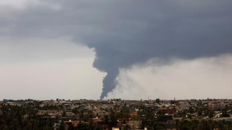 Plumes of smoke rise in the sky after a rocket hit a fuel storage tank near the airport road in Tripoli, during clashes between rival militias