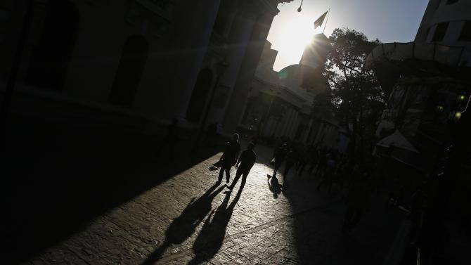 People walk at plaza Bolivar square in downtown Caracas