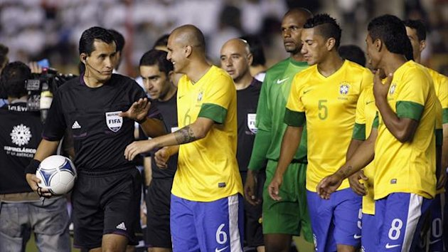 Brazil players walk of the pitch after floodlights failed in their friendly against Argentina