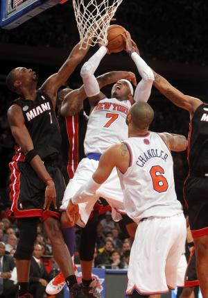 New York Knicks' Carmelo Anthony (7) shoots against, from left, Miami Heat's Chris Bosh (6), Dwyane Wade (3) and Rashard Lewis (9) during the first half of an NBA basketball game, Friday, Nov. 2, 2012, in New York. (AP Photo/Jason DeCrow)