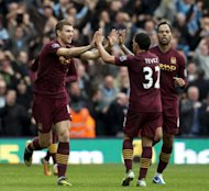 Manchester City's forward Edin Dzeko (L) celebrates with his teammates after scoring against West Bromwich Albion during their English Premier League football match at The Hawthorns. Manchester City won the game 2-1