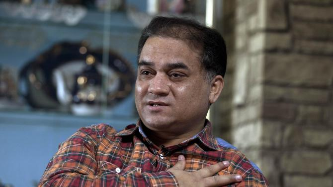 FILE - In this Monday, Feb. 4, 2013 file photo, Ilham Tohti, an outspoken scholar of China's Turkic Uighur ethnic minority, speaks during an interview at his home in Beijing, China. Police have taken away Ilham Tohti, and raided his home, seizing computers, cellphones and even his students' theses, his wife Guzaili Nu'er said Thursday, Jan. 16, 2014. (AP Photo/Andy Wong)