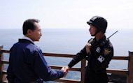 South Korean President Lee Myung-Bak shakes hands with a police guard on August 10, during a visit to remote islands disputed with Japan -- known as Dokdo in Korea and Takeshima in Japan. Lee said his unprecedented visit to islands was intended to press Tokyo to settle grievances left over from its colonial rule