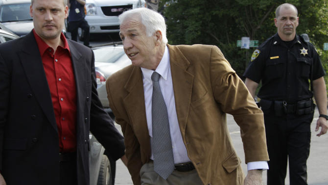 Former Penn State University assistant football coach Jerry Sandusky, center, arrives at the Centre County Courthouse in Bellefonte, Pa., Friday, June 22, 2012. Sandusky is charged with 51 counts of child sexual abuse involving 10 boys over a period of 15 years.  (AP Photo/Gene J. Puskar)