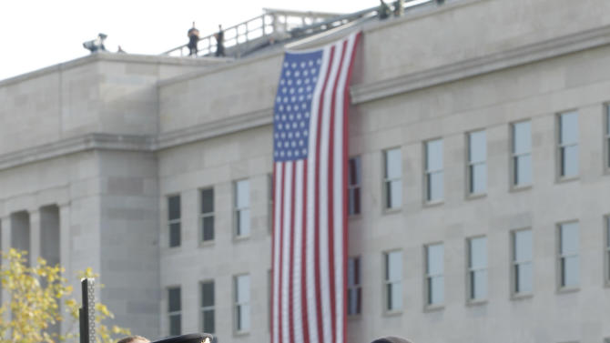 Visitors gather near a flag marking the spot where on September 11, 2001 a passenger jet was flown into the Pentagon building, in Washington