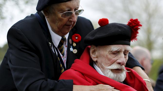 Canadian WWII veteran Sanderson is wrapped in a blanket before the start of a ceremony on the eve of the 70th anniversary of the liberation of the Netherlands at the Canadian War Cemetery in Holte