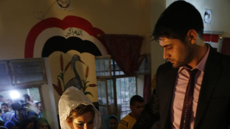 Displaced Iraqis who fled from the violence in Mosul walk during their wedding at a school in Baghdad
