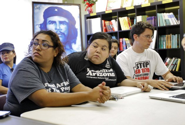 Community members Leticia Ramirez, left, Jovana Renteria, center, and Puente Movement Comunication Director B. Loewe react to the United States Supreme Court decision regarding Arizona's controversial immigration law, SB1070, come down at the Puente Movement offices, Monday, June 25, 2012, in Phoenix. The Supreme Court struck down key provisions of Arizona's crackdown on immigrants Monday but said a much-debated portion on checking suspects' status could go forward. (AP Photo/Matt York)