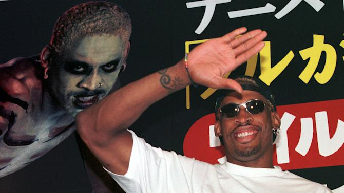 """FILE - In this July 28, 1997, file photo, former NBA basketball player Dennis Rodman waves to his fans as he arrives at a Tokyo publishing house to promote his autobiography """"Walk on the Wild Side.""""  Rodman, one of basketball's most outrageous personalities, has written a book for children. The Hall of Famer's book, """"Dennis The Wild Bull,"""" came out Wednesday, Jan. 30, 2013. (AP Photo/Koji Sasahara, File)"""