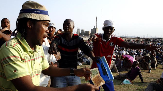 Miners sing and dance in Lonmin Platinum Mine near Rustenburg, South Africa, Tuesday, Sept. 18, 2012. Striking miners have accepted a company offer of a 22% overall pay increase to end more than five weeks of crippling and bloody industrial action. (AP Photo/Themba Hadebe)