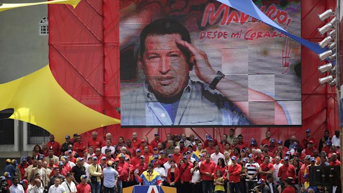 A large image of late President Hugo Chavez hangs behind acting President Nicolas Maduro speaking to supporters after he registered his candidacy to replace Chavez outside the national electoral council in Caracas, Venezuela, Monday, March 11, 2013. Presidential elections were announced to take place on April 14, after Maduro announced on March 5 that Chavez had died. (AP Photo/Fernando Llano)