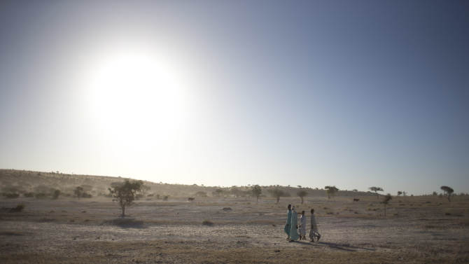 In this Nov. 2, 2012 photo, young men walk in the wadi alongside Louri village, in the Mao region of Chad. Climate change has meant that the normally once-a-decade droughts are now coming every few years, decimating food production. (AP Photo/Rebecca Blackwell)